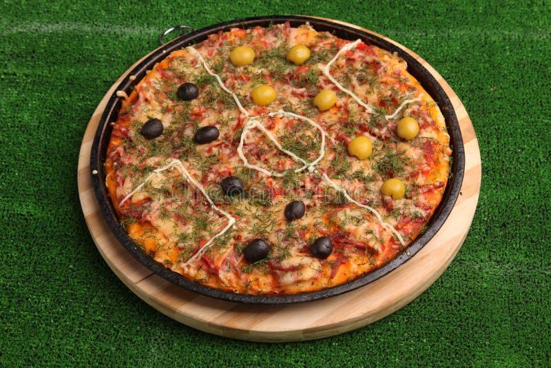 Pizza do futebol no campo verde imagens de stock royalty free