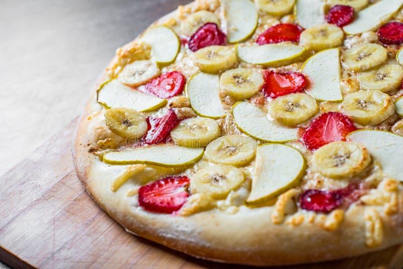 Pizza doce com mozzarella, ma??, banana, morangos Pizza da sobremesa do fruto na tabela de madeira foto de stock