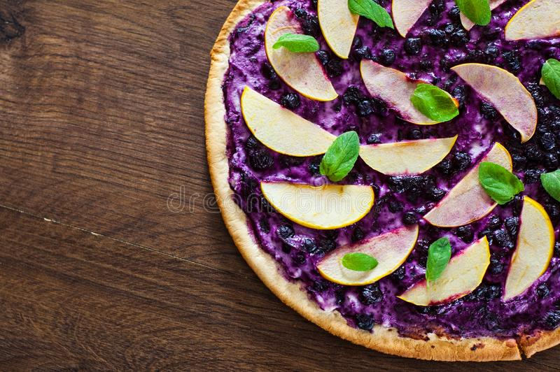 Pizza doce com queijo da ricota, mirtilo e maçã das fatias pizza da sobremesa em um de madeira fotografia de stock royalty free