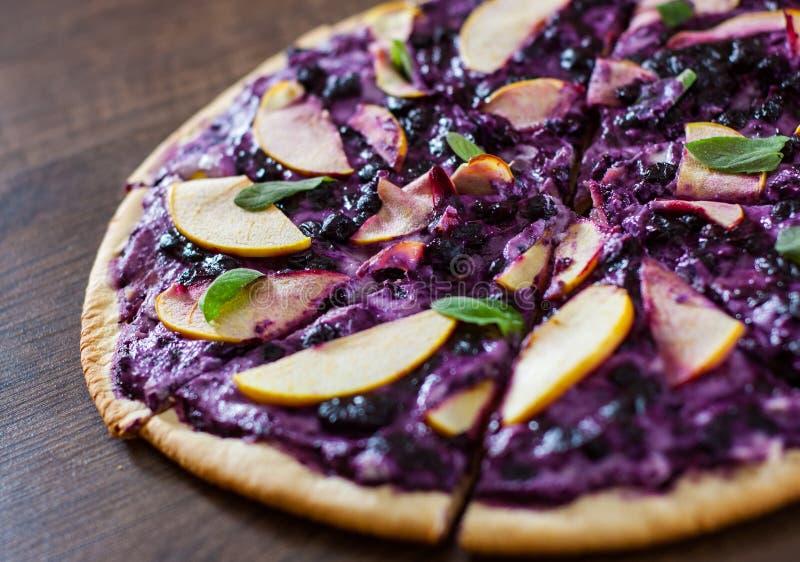 Pizza doce com queijo da ricota, mirtilo e maçã das fatias pizza da sobremesa em um de madeira imagem de stock