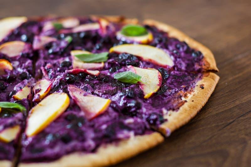 Pizza doce com queijo da ricota, mirtilo e maçã das fatias pizza da sobremesa em um de madeira fotografia de stock