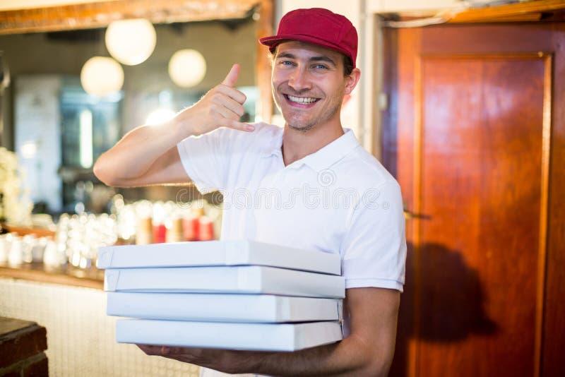 Pizza doręczeniowego mężczyzna mienia pizzy pudełka robi telefonowi gestykulować obrazy stock
