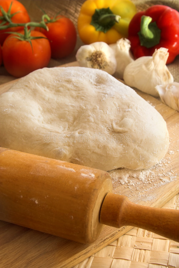 Pizza dough and rolling pin. With vegetables royalty free stock images