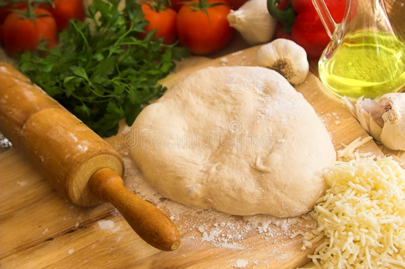 Pizza dough and rolling pin. With olive oil and vegetables on wooden board royalty free stock photography