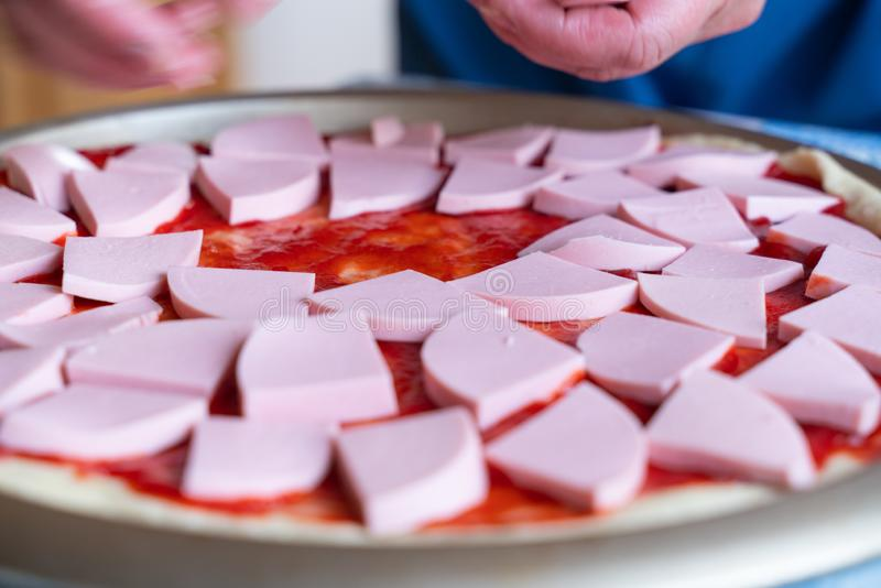pizza dough smeared with ketchup and with slices of sausage as background stock photography