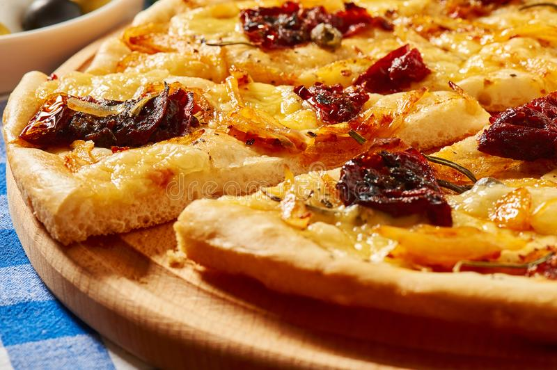 Pizza with dry tomatoes, onion and cheese on a wooden plate royalty free stock photography