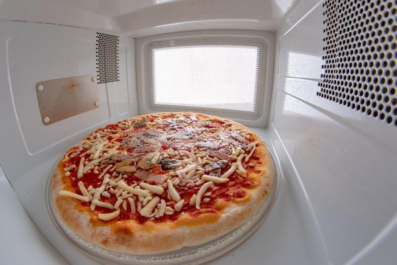 Pizza du supermarch? dans la micro-onde Aliments de pr?paration rapide pr?par?s dans la cuisine ? la maison images stock