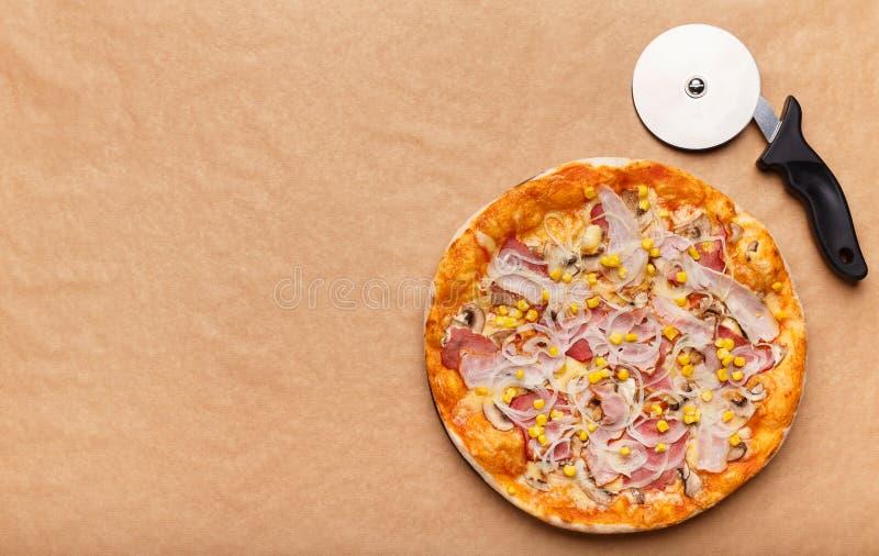 Pizza e taglierina calde italiane sul fondo della carta del mestiere immagine stock libera da diritti