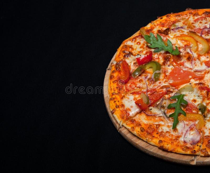 Pizza em uma placa de madeira com uma cópia do lugar em um fundo preto imagens de stock