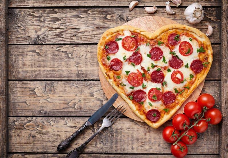 Pizza en forma de corazón con los salchichones, tomates y fotos de archivo