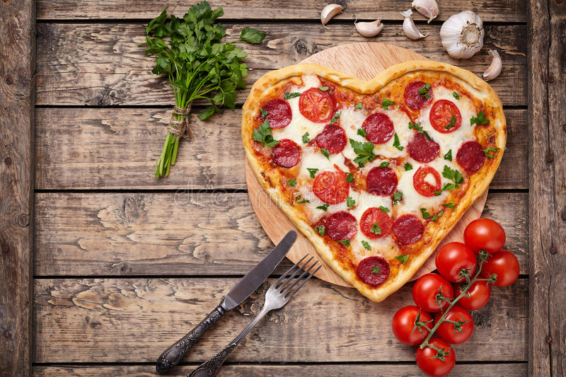 Pizza en forma de corazón del día de tarjetas del día de San Valentín con los salchichones imagen de archivo libre de regalías