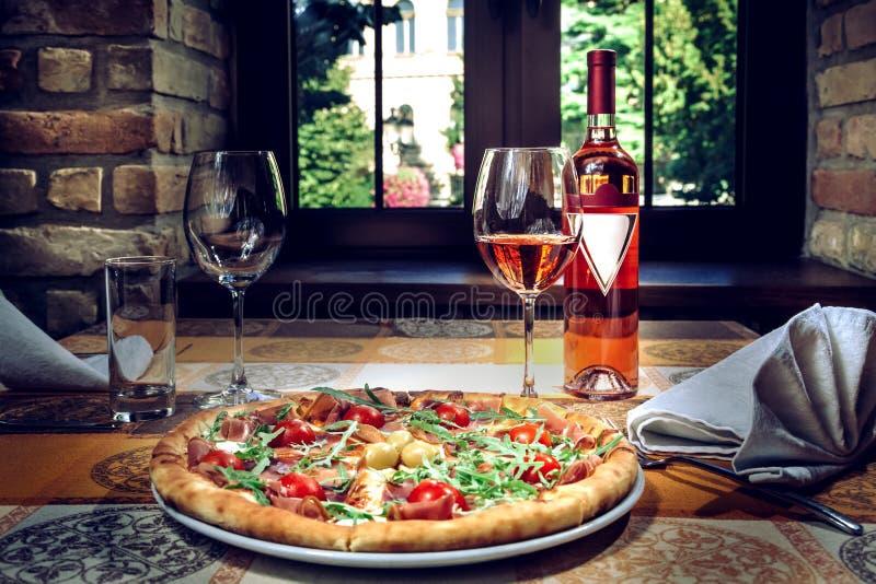 Pizza en rode wijn op de lijst stock foto
