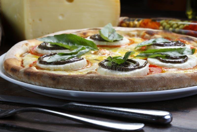 Pizza en una placa fotografía de archivo libre de regalías