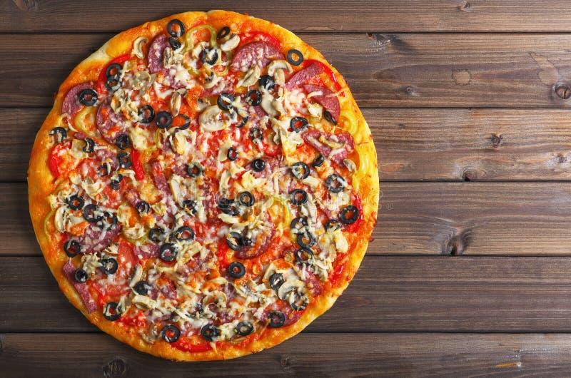 Pizza en una tabla de madera imagenes de archivo