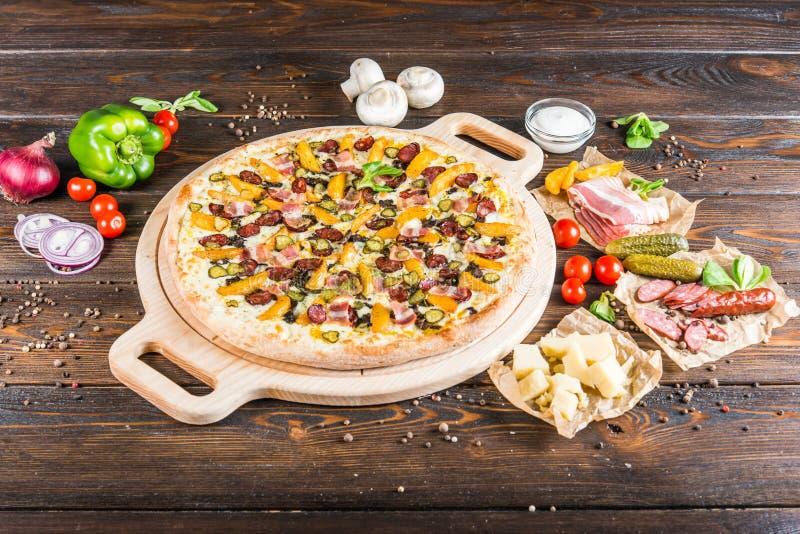 Pizza enorme con la salchicha, pepino conservado en vinagre, tocino en un cutt redondo fotografía de archivo libre de regalías