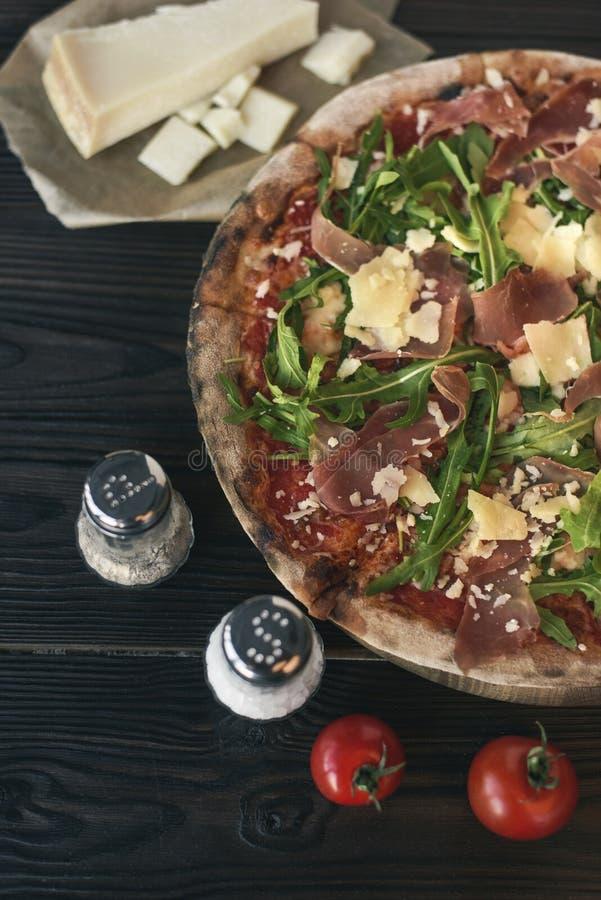 Pizza, especiarias e cutelaria na superfície de madeira escura foto de stock