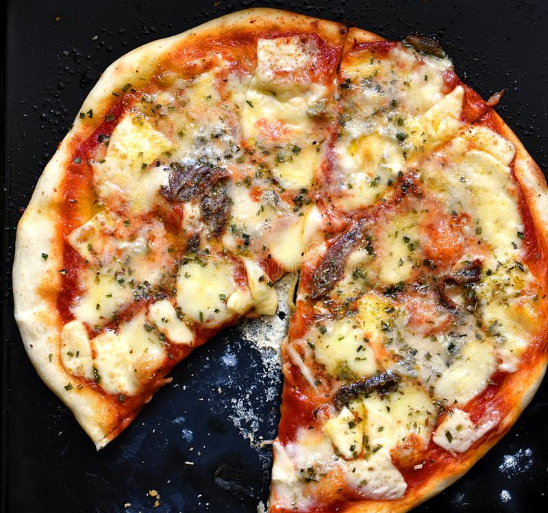 Pizza faite maison d'anchois avec une tranche mangée sur une casserole noire images stock