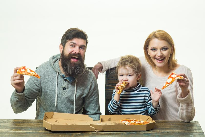 Pizza family. Mother, father and child, a small son with parents eating pizza. Family dinner with mom and dad. Italian royalty free stock photography