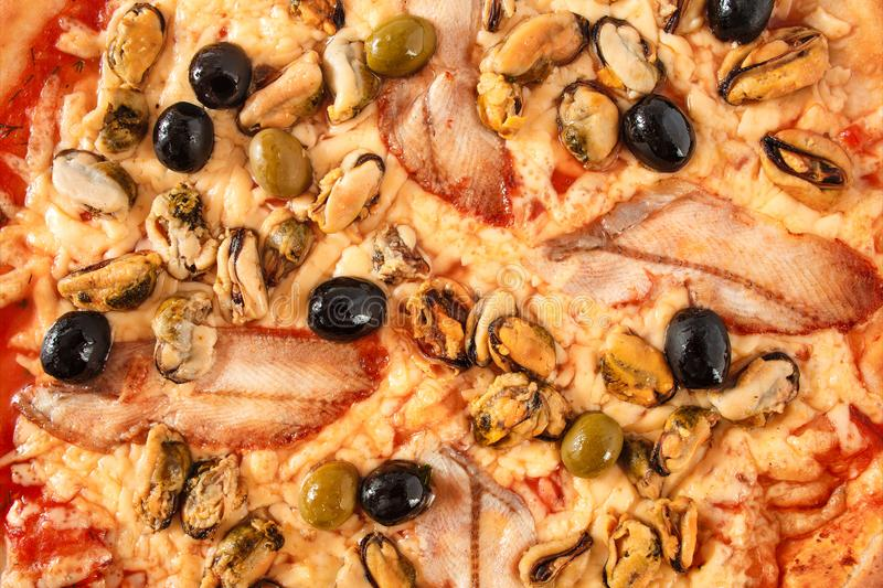 Pizza with fish eel, mussel, black and green olives, cream cheese close-up, selective focus, macro stock photography