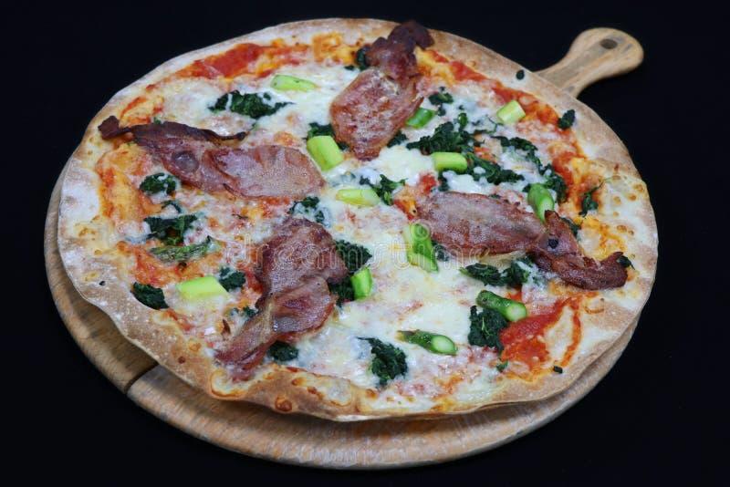 Pizza florentine de croûte mince avec le lard et les épinards image stock