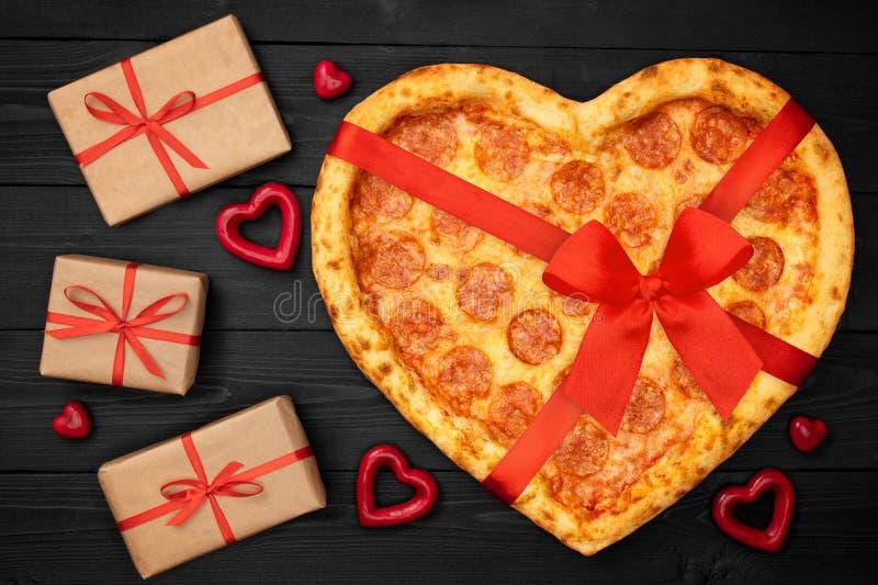 Pizza formte Herz mit rotem Bogenband und Präsentkarton für Valentinstagkonzept auf rustikalem schwarzem Hintergrund Beschneidung lizenzfreie stockbilder