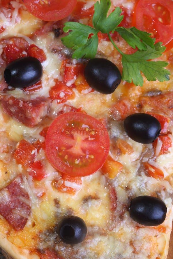 Pizza från en salami, en skinka och tomater på en trätabell royaltyfri bild