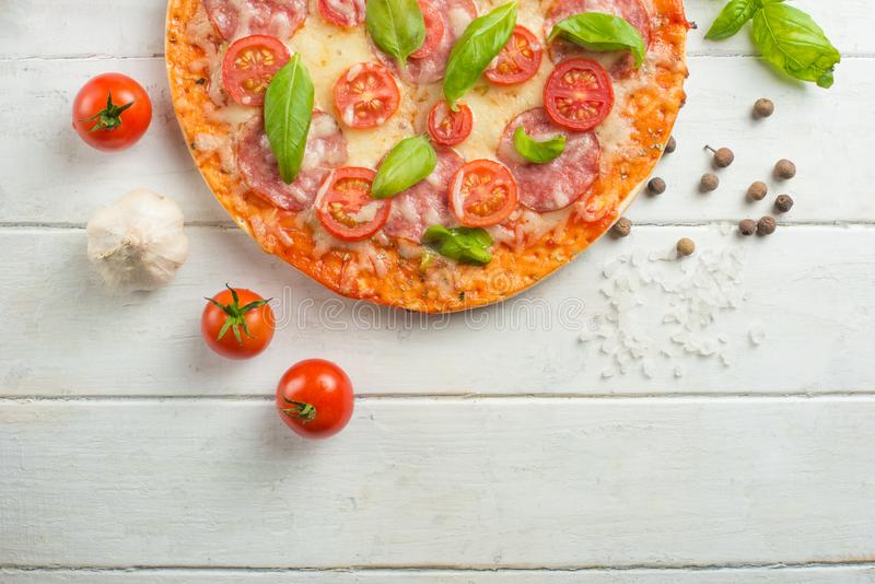 Pizza fraîche avec les tomates, le fromage et le salami sur un plan rapproché en bois de table photographie stock
