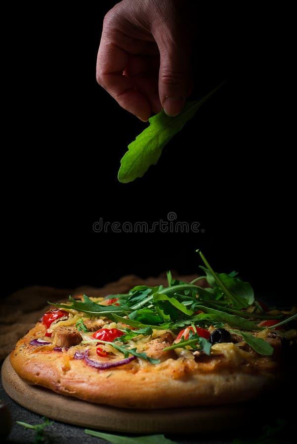 Pizza fraîche avec les tomates, le fromage, le poulet et les champignons La pizza italienne a arrosé l'arugula, fatigué du travai images stock