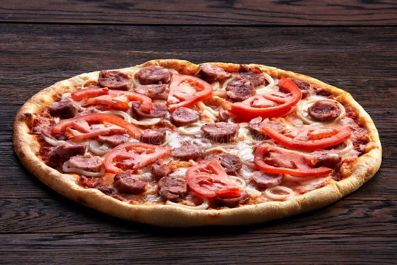 Pizza fresca com tomates, queijo, cebolas e salsicha no close up de madeira da tabela fotografia de stock