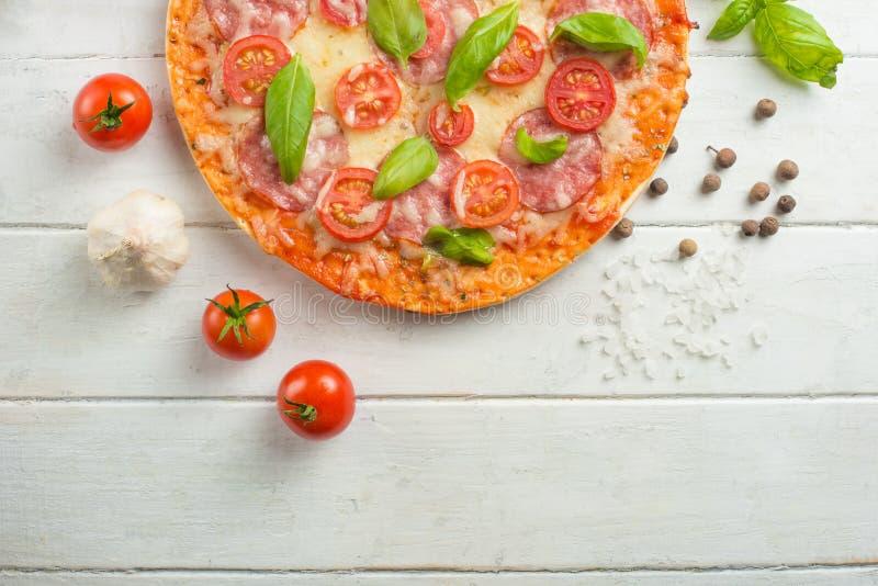 Pizza fresca com tomates, queijo e salame em um close-up de madeira da tabela fotografia de stock