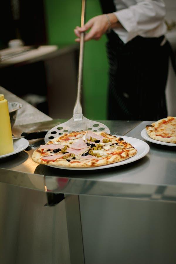 Pizza fresca in pizzeria Il cuoco unico ha fatto la pizza e la presa al piatto del rhe fotografie stock libere da diritti