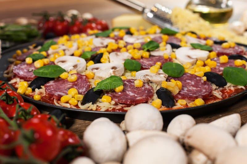 Pizza fresca pronta ad essere cucinato con tutti gli ingredienti intorno immagini stock