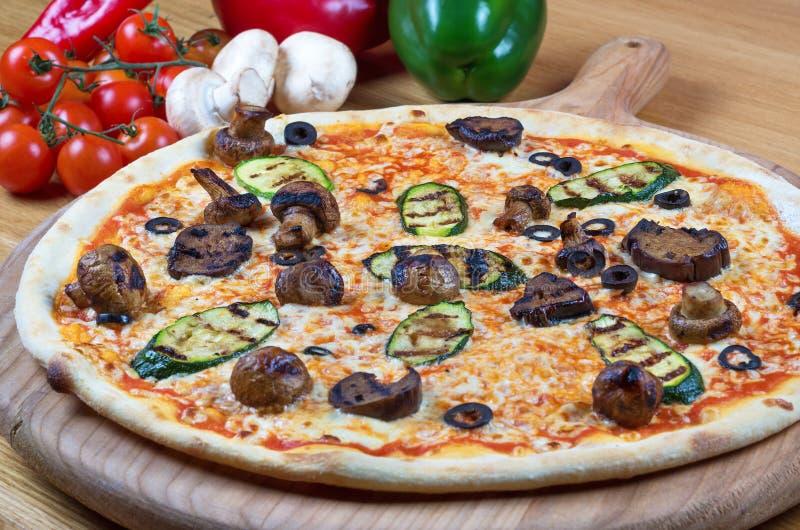 Pizza fresca saboroso decorada com cogumelos e abobrinha no fundo de madeira imagem de stock