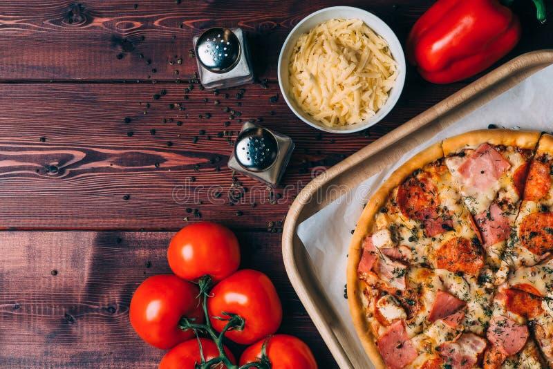 Pizza fresca saboroso, vista superior, tomates, pimenta búlgara, queijo raspado, especiarias como ingredientes na tabela de madei imagem de stock
