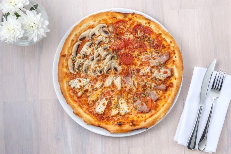 Pizza fyra säsonger på en ljus träbakgrund arkivbild