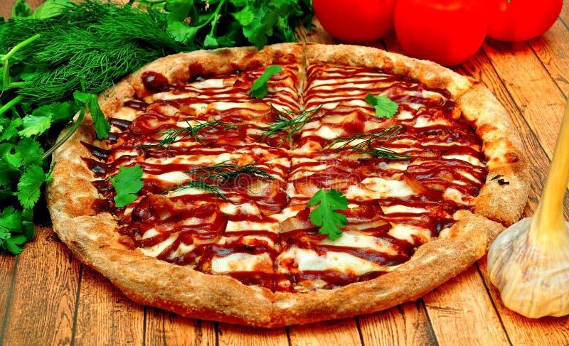 Pizza grande com um assado em uma tabela de madeira fotos de stock royalty free