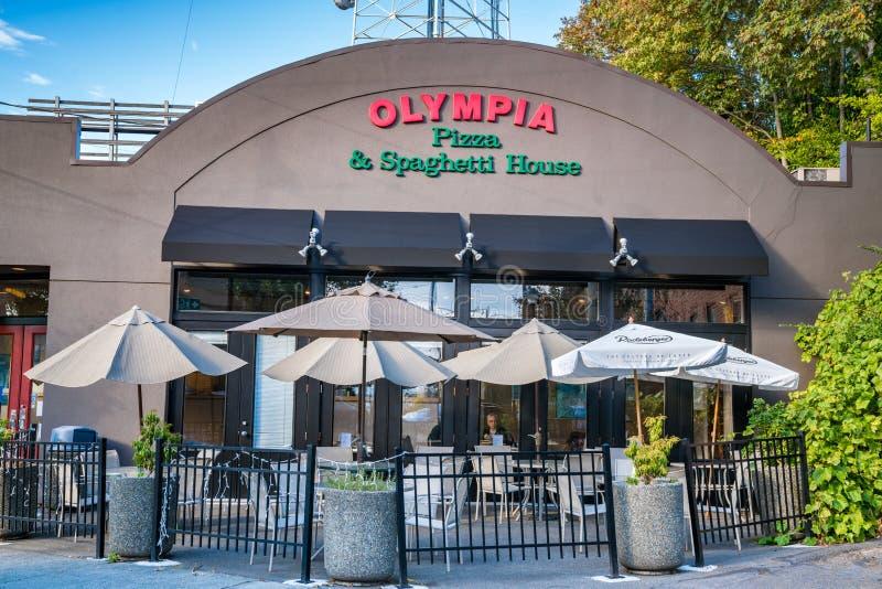 Pizza griega de servicio del estilo de la casa de Olympia Pizza y de los espaguetis imagen de archivo