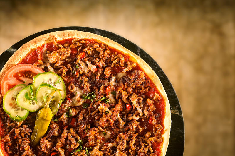 Pizza with ground meat and vegetable toppings. Cropped top down view on single pizza with ground meat, cucumber, tomatoes and hot pepper toppings royalty free stock image