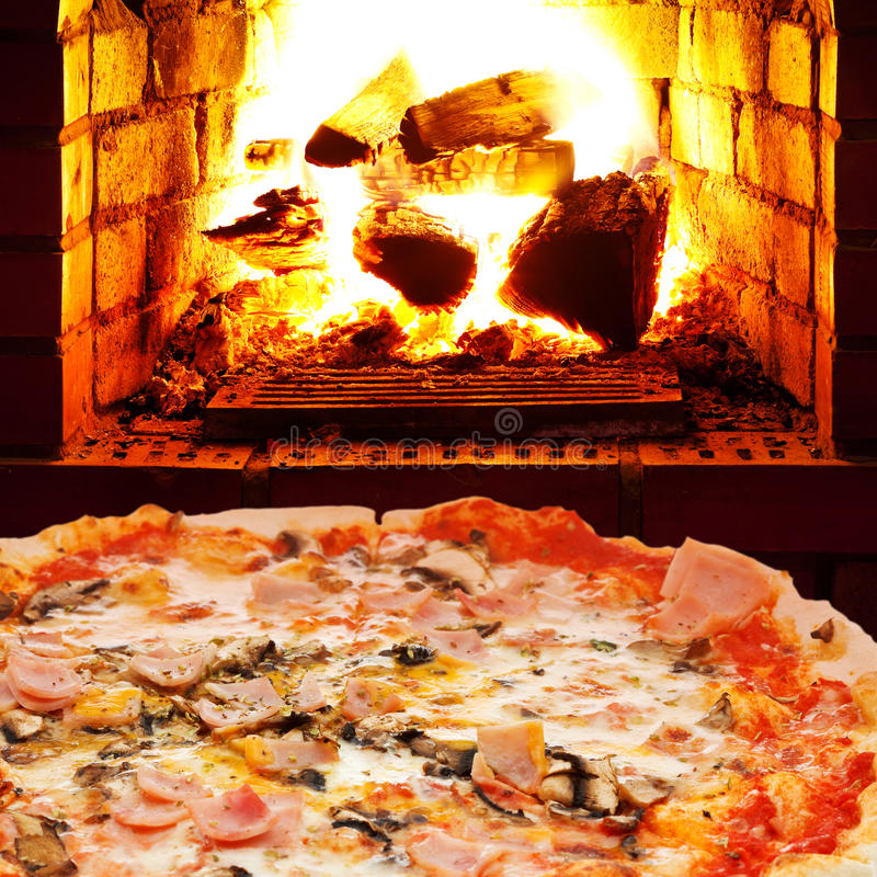 Pizza with ham, mushroom and open fire in oven. Italian pizza with ham and mushrooms and open fire in wood burning oven royalty free stock photography