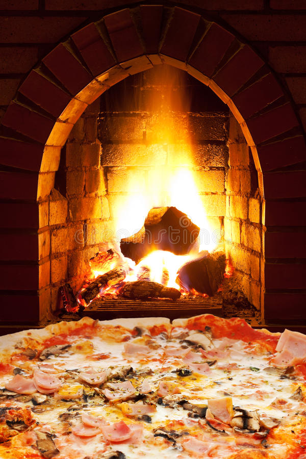 Pizza with ham, mushroom and open fire in stove. Italian pizza with ham and mushrooms and open fire in wood burning stove stock image