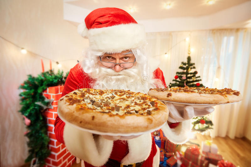 Pizza in the hands of Santa Claus at Christmas, happy new year c. Lose-up stock photography