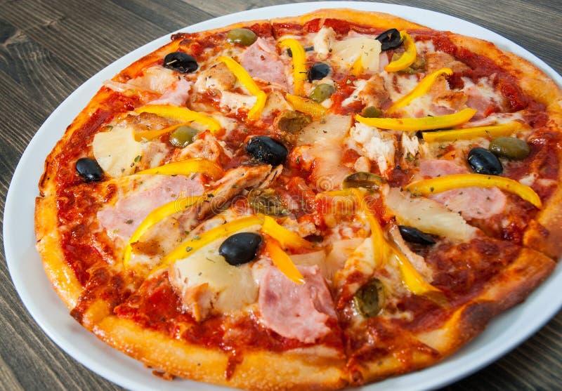 Pizza havaiana com abacaxi, presunto, galinha, queijo, azeitonas e vegetais imagem de stock royalty free