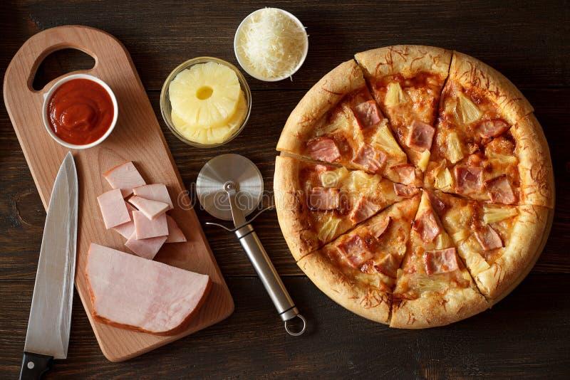 Pizza hawaiana casalinga con l'ananas, il prosciutto, il formaggio e la salsa al pomodoro su fondo di legno fotografie stock
