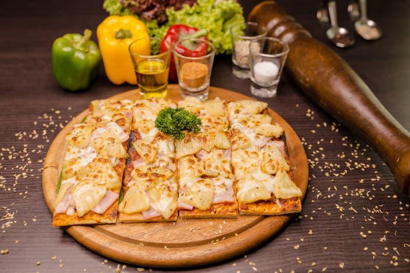 Pizza hawaiana en la placa de madera de la textura foto de archivo