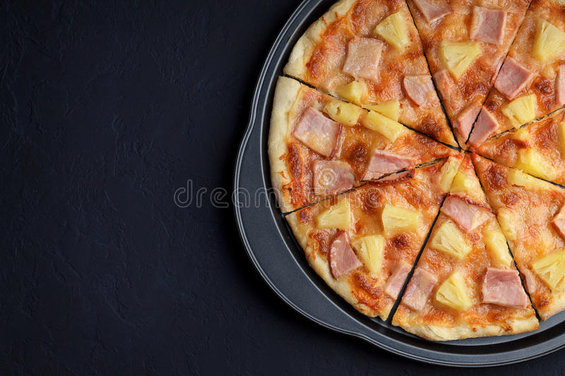 Pizza hawaii on dark stone background. royalty free stock images