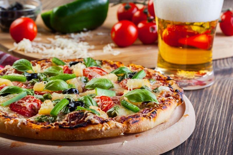 Pizza hawaii med öl arkivbilder