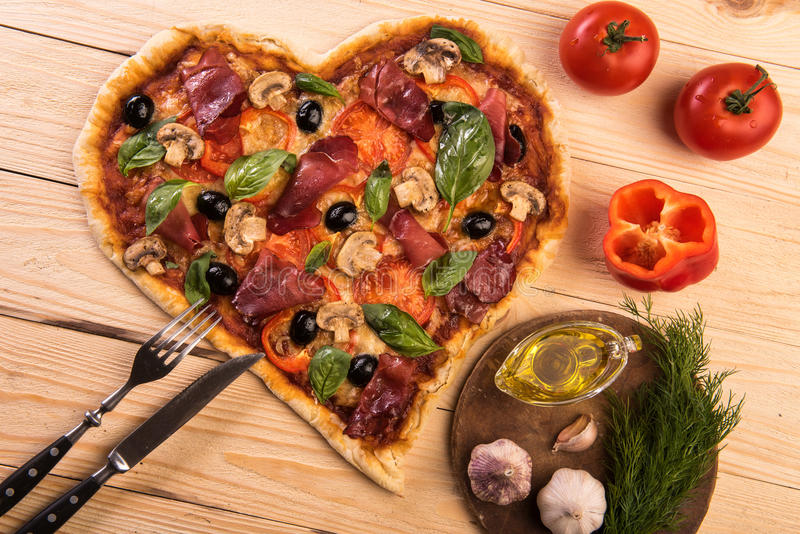 Pizza heart love Valentine`s Day romantic Italian restaurant dinner food. Prosciutto, olives, tomatoes, parsley, basil. And mozzarella cheese meal on wooden stock image