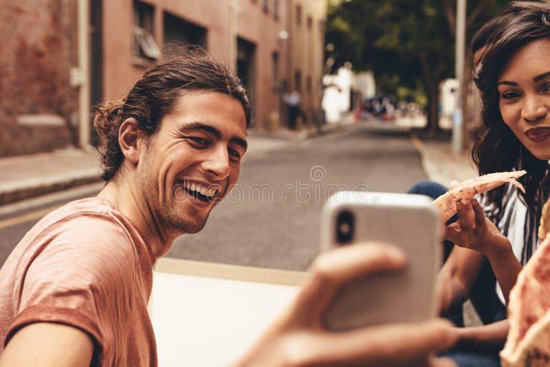 Pizza hebben en vrienden die selfie nemen stock foto
