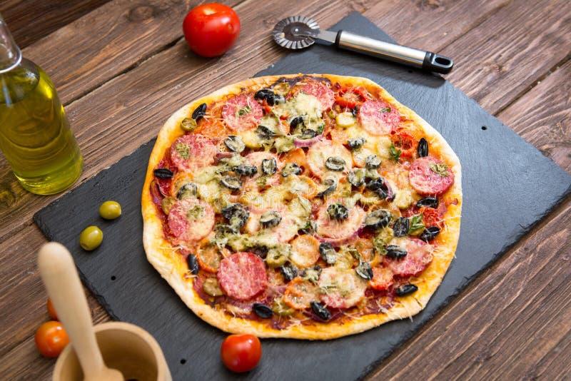 Pizza hecha en casa con la salchicha de los salchichones en la tabla fotos de archivo