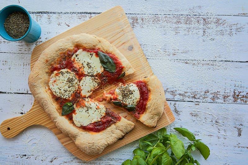 Pizza hecha en casa con la salsa de tomate, queso de la mozzarella y padano y albahaca frescos machacados imágenes de archivo libres de regalías